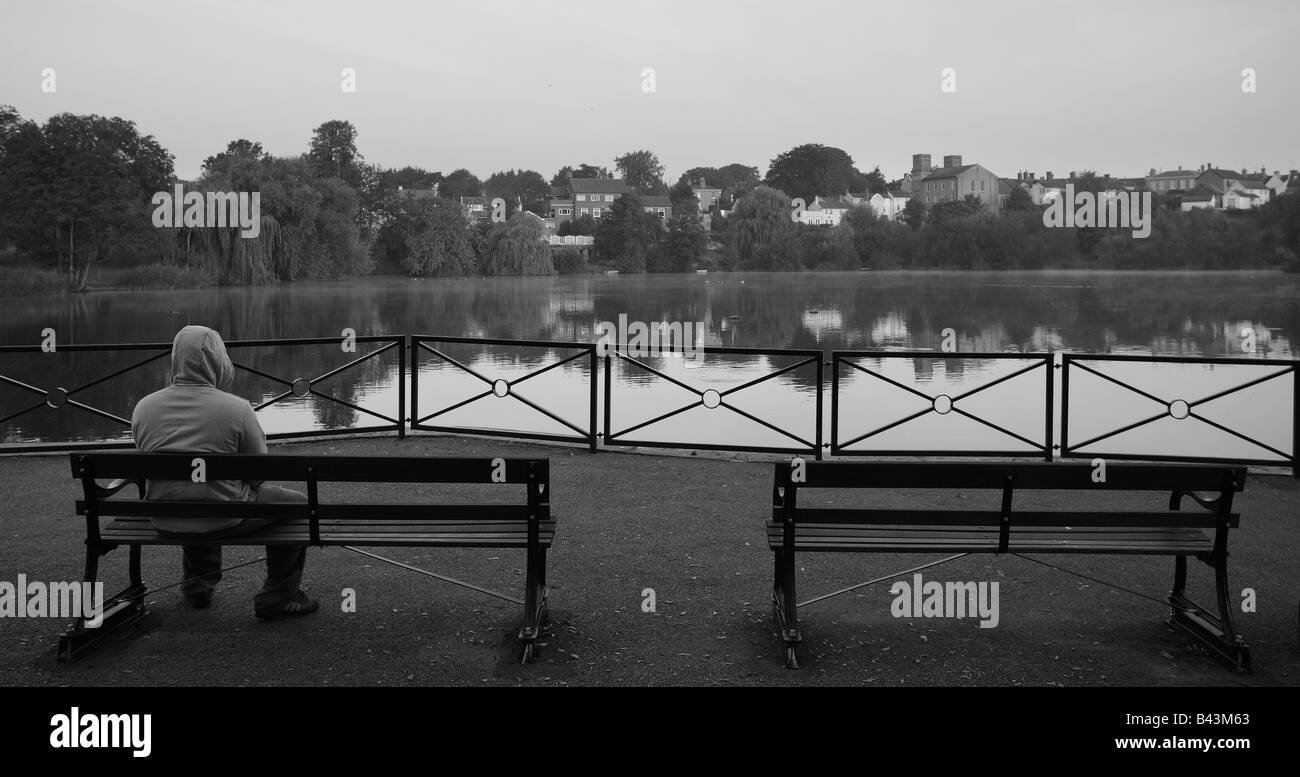 Hooded figure on bench in a park. - Stock Image