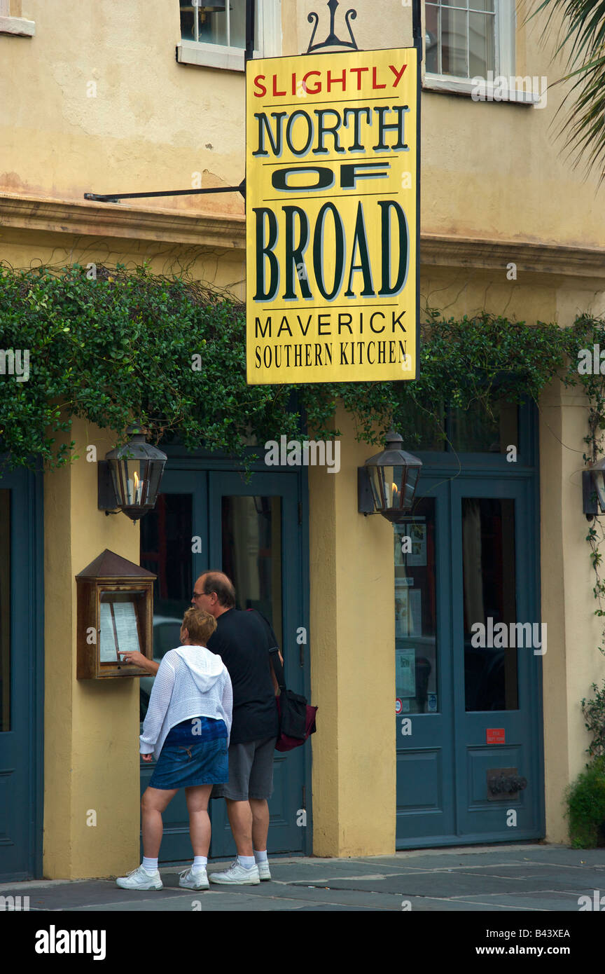 A couple looks at the menu at SNOB Slightly North of Broad restaurant along East Bay Street in historic Charleston - Stock Image
