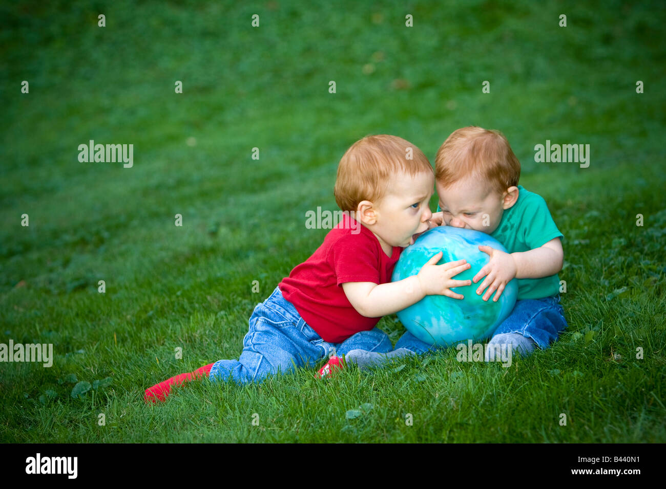 Young redheaded baby boys sitting outside on grass playing with ball - Stock Image
