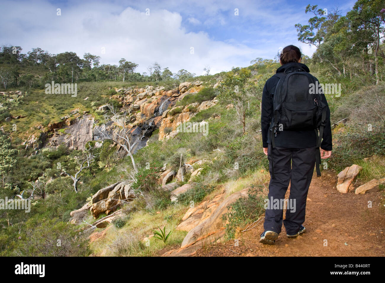 A mid 20s woman bushwalking along a track next to the waterfall at Ellis Brook in the Darling Scarp. Perth, Western - Stock Image
