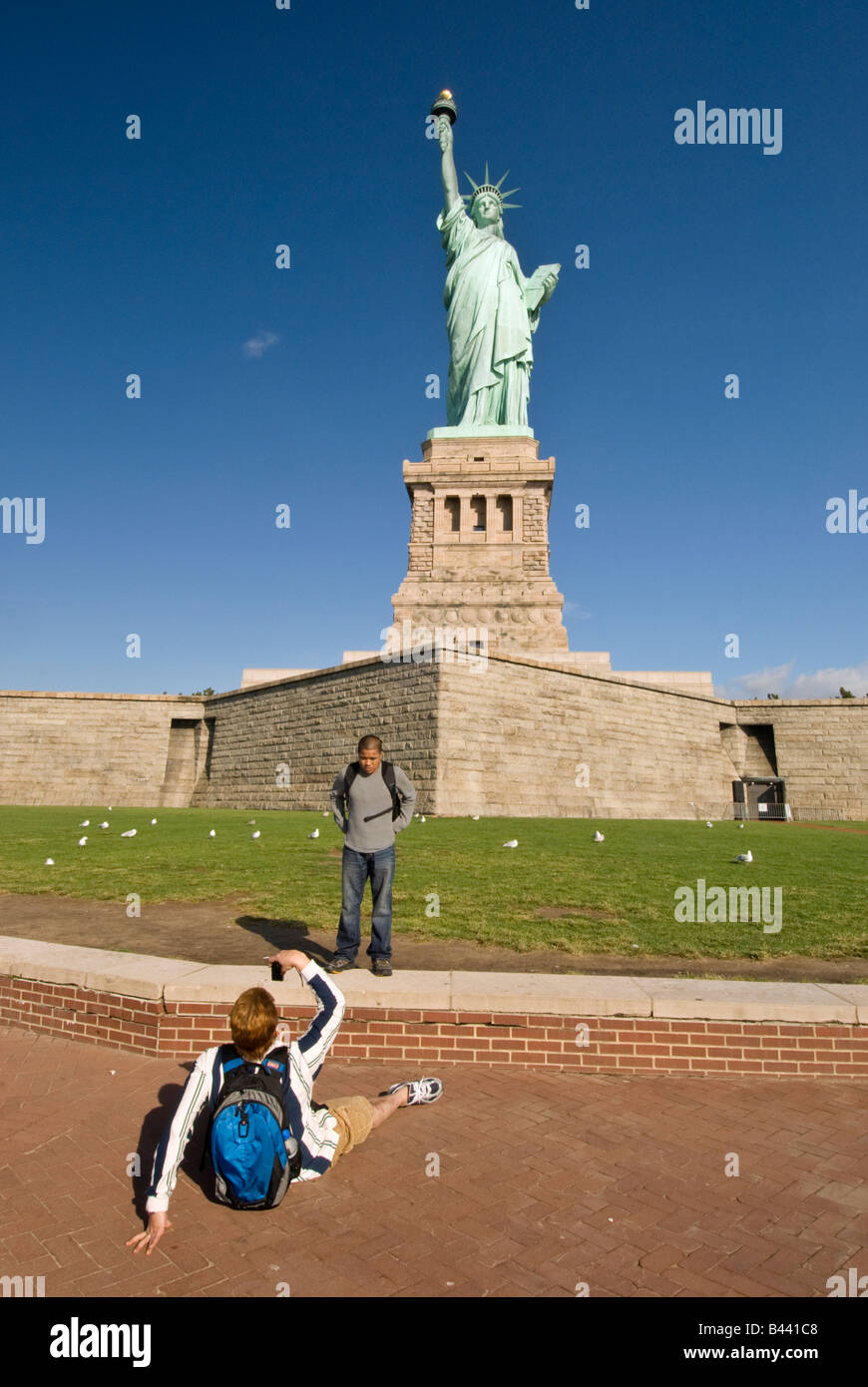 Tourists taking pictures at the Statue of Liberty in New York City - Stock Image