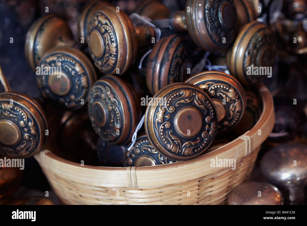 A wicker basket of brass doorknobs on display in an architectural antiques store - Stock Image