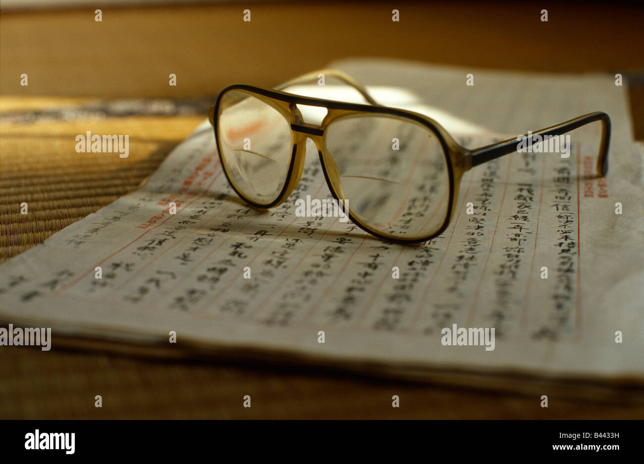 Old glasses on top of an old letter written in Chinese. - Stock Image