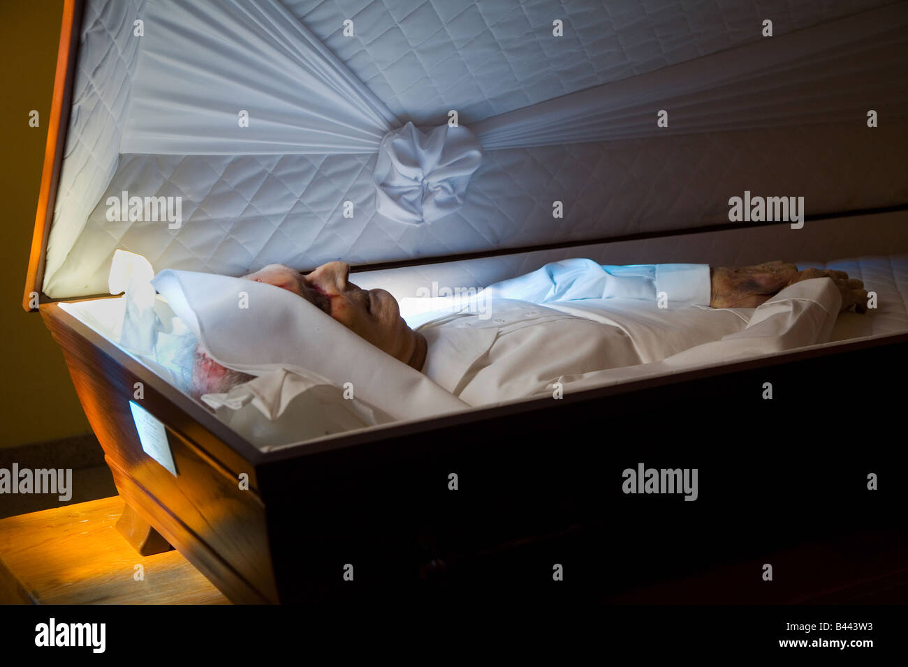a man is lying in his coffin for relatives to say goodbye - Stock Image