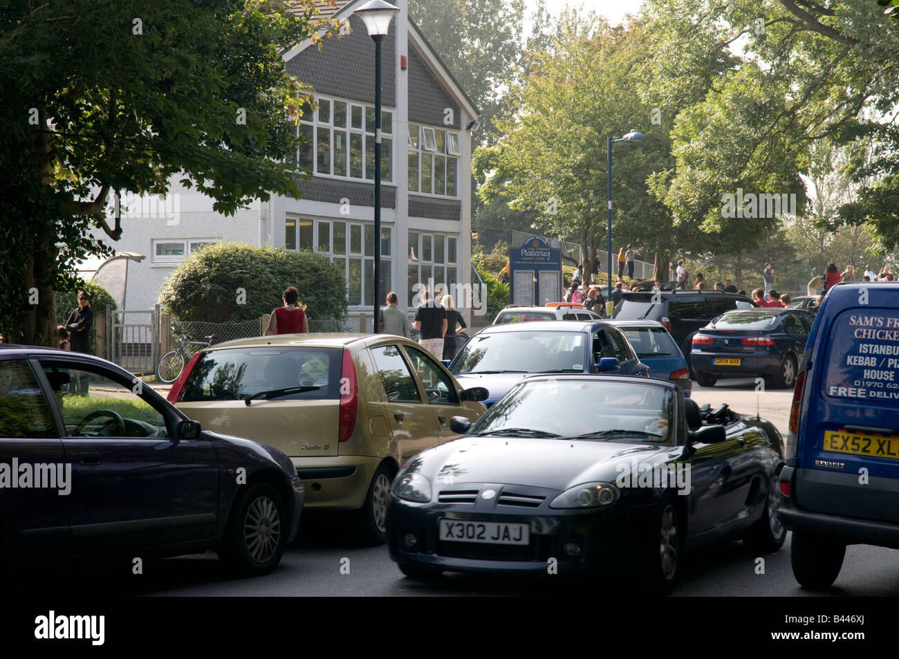 Queues of cars - parents waiting to collect children outside Plascrug Primary school Aberystwyth Wales UK - Stock Image