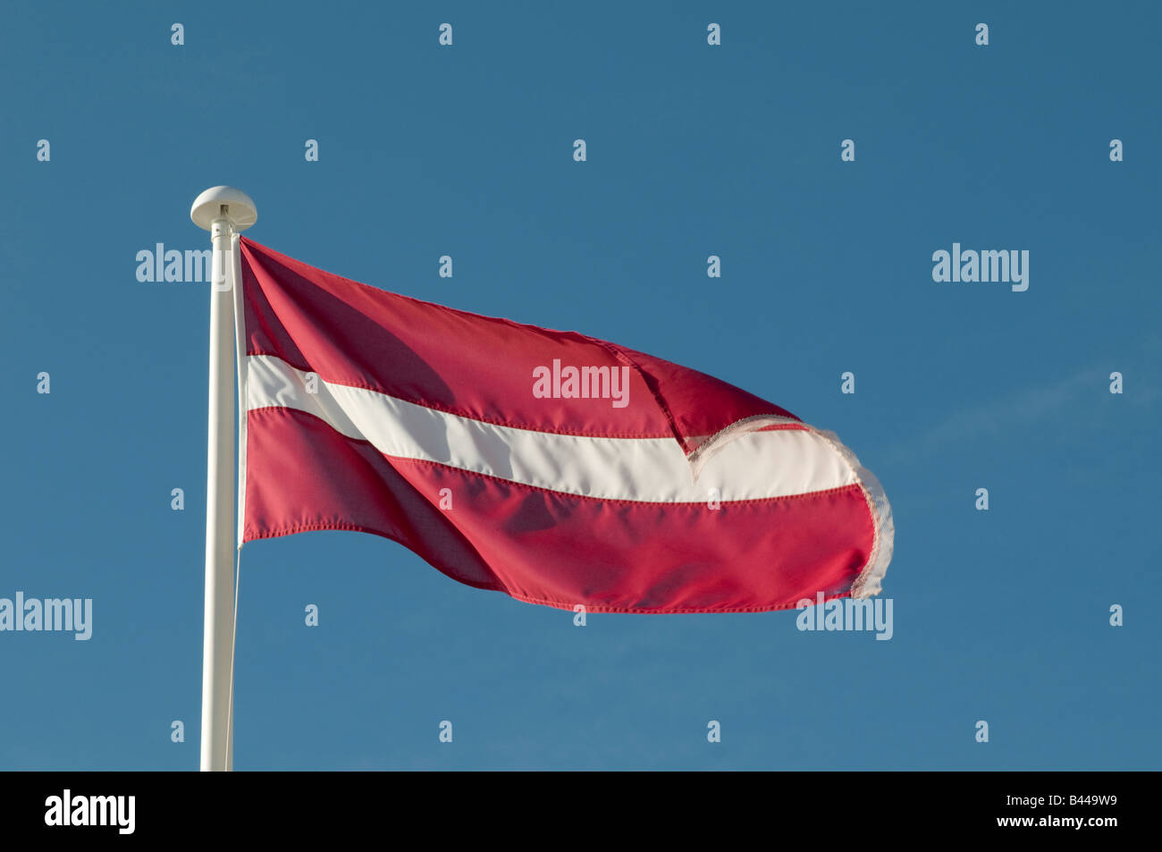 Latvian flag white stripe on red background against blue sky - Stock Image