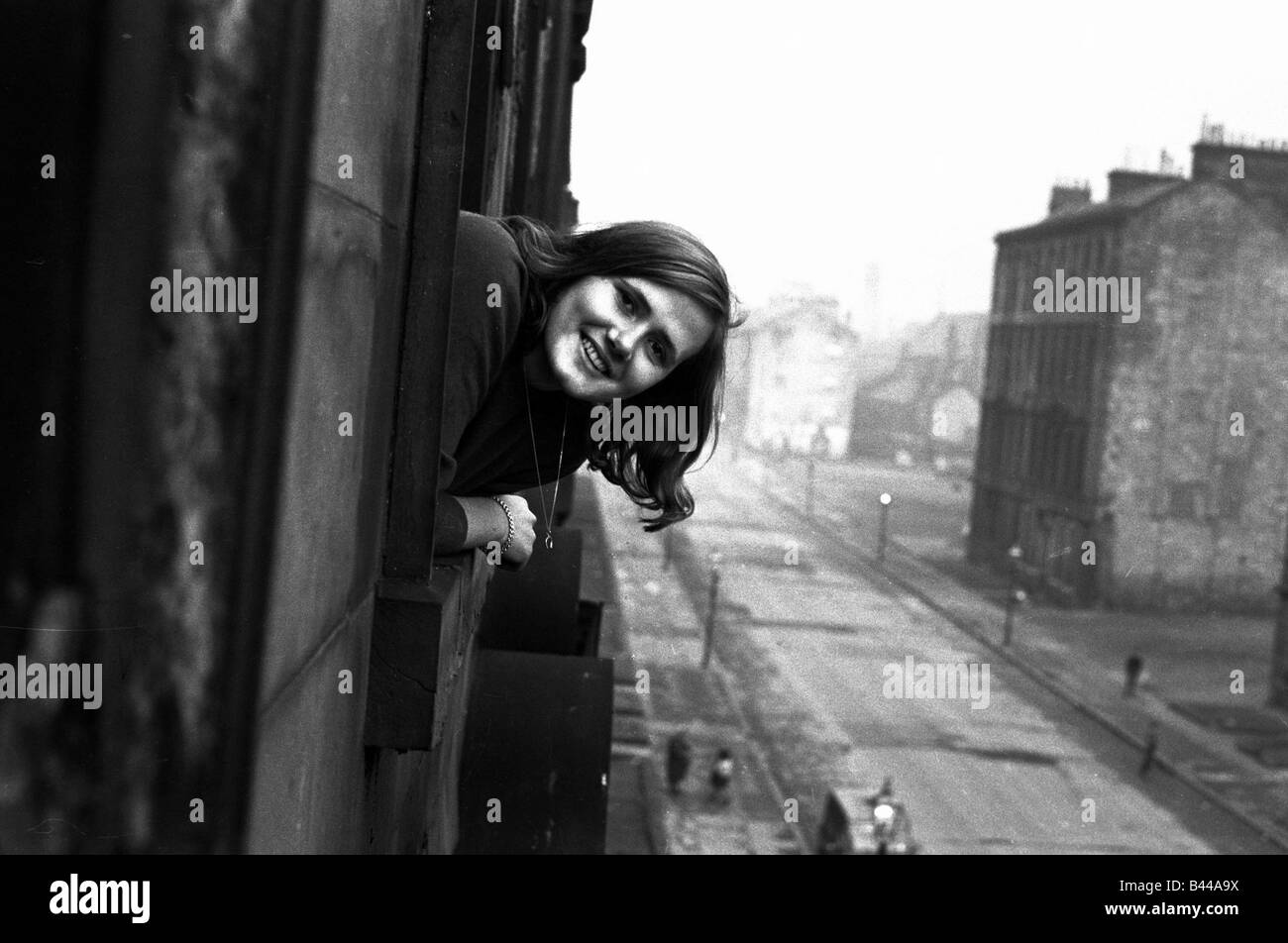 A youth worker pops her head out of one of the windows in a housing slums in the Gorbals district of Glasgow January Stock Photo