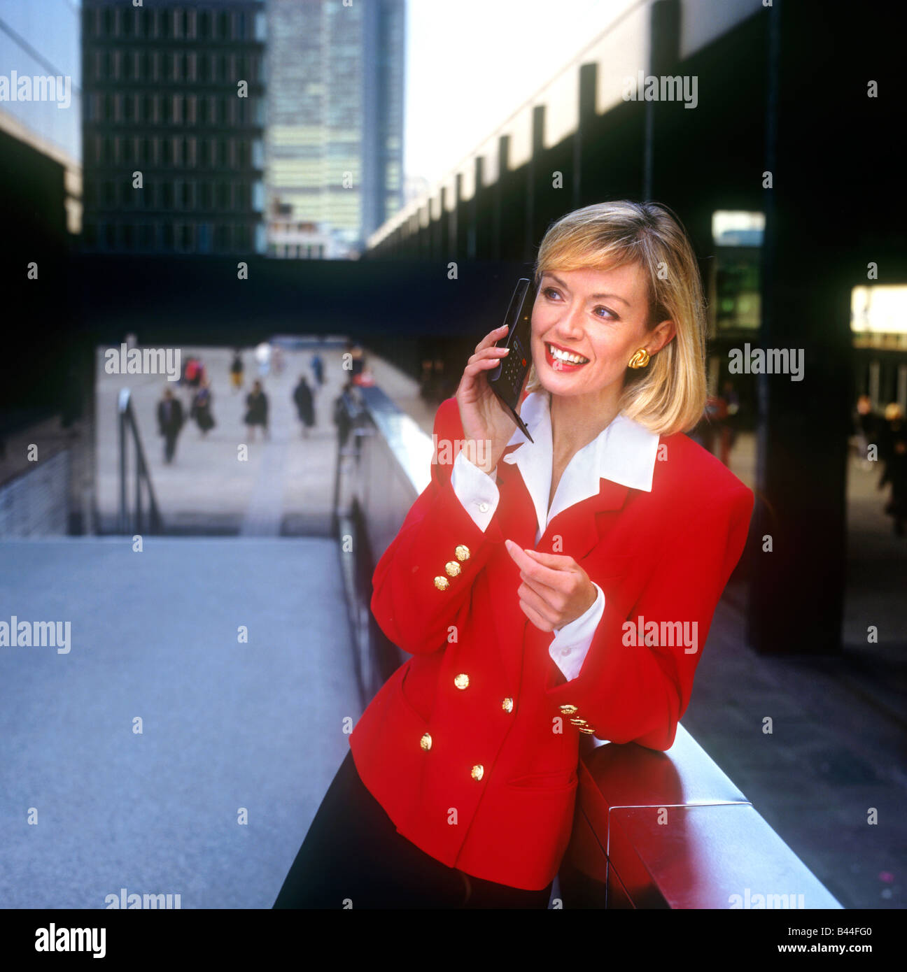 1980's advertising photo model image illustrating executive businesswoman with early first generation flip open - Stock Image
