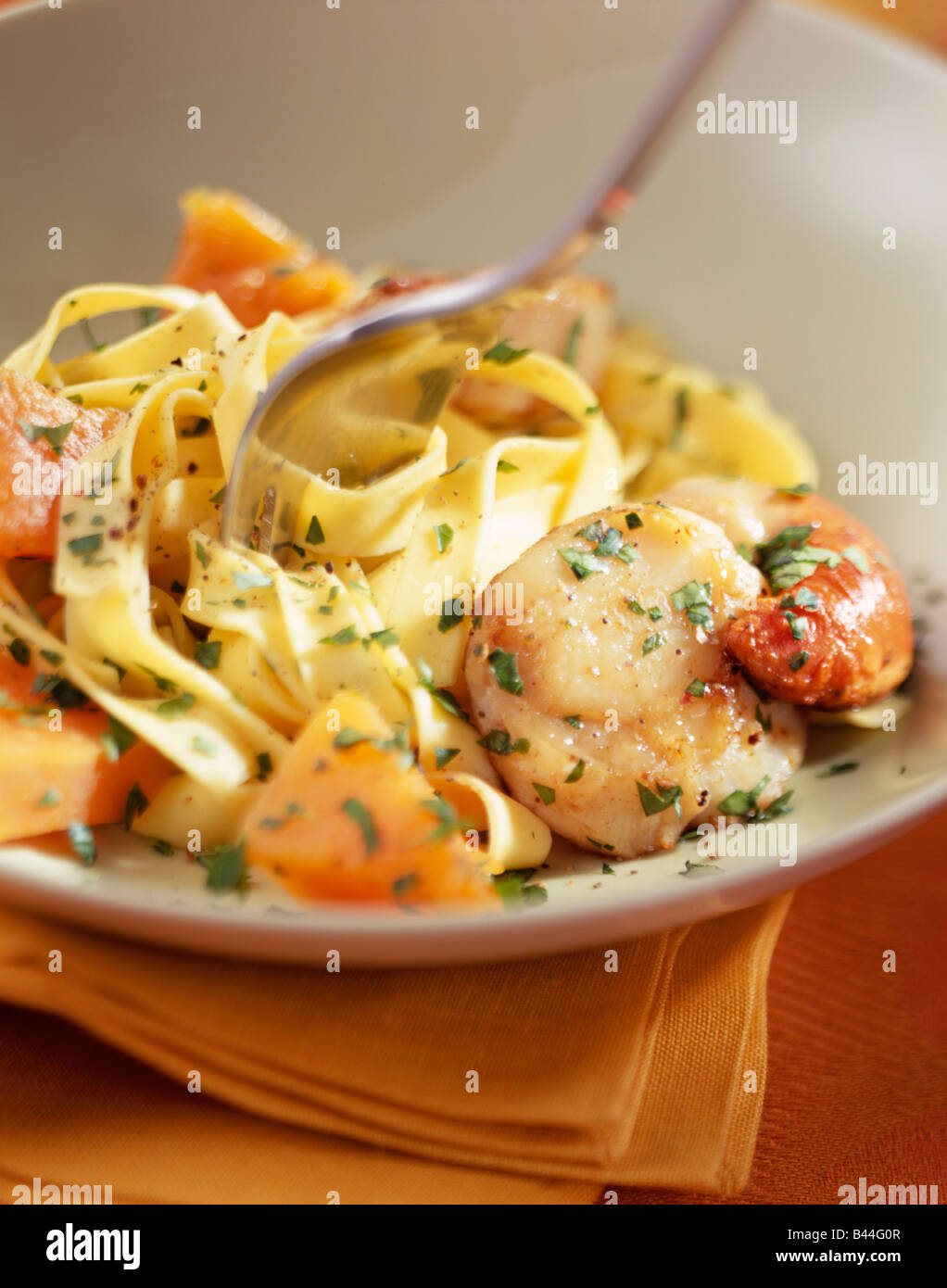 Tagliatelles with scallpos and pumpkin Stock Photo