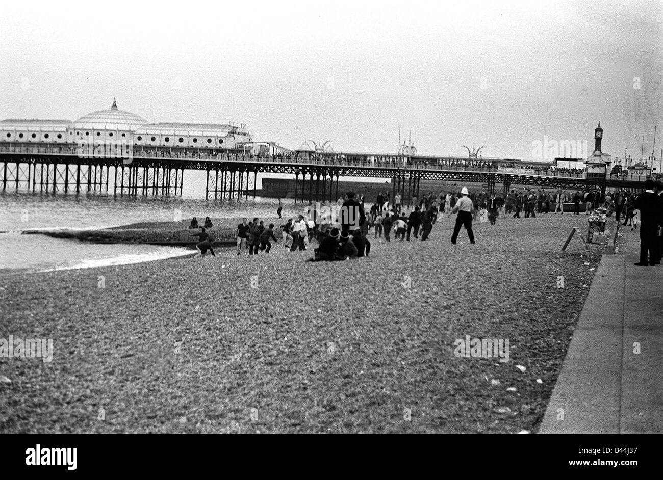 Mods and rockers clash on Brighton beach during bank 1964 holiday - Stock Image