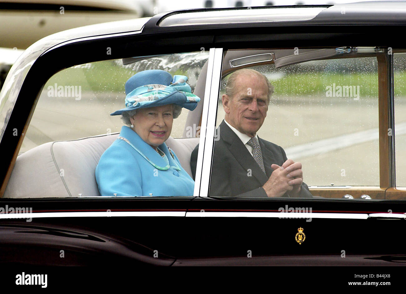 HRH Queen Elizabeth II May 2002 At Glasgow airport accompanied by Prince Philip Duke of Edinburgh Wearing blue hat - Stock Image