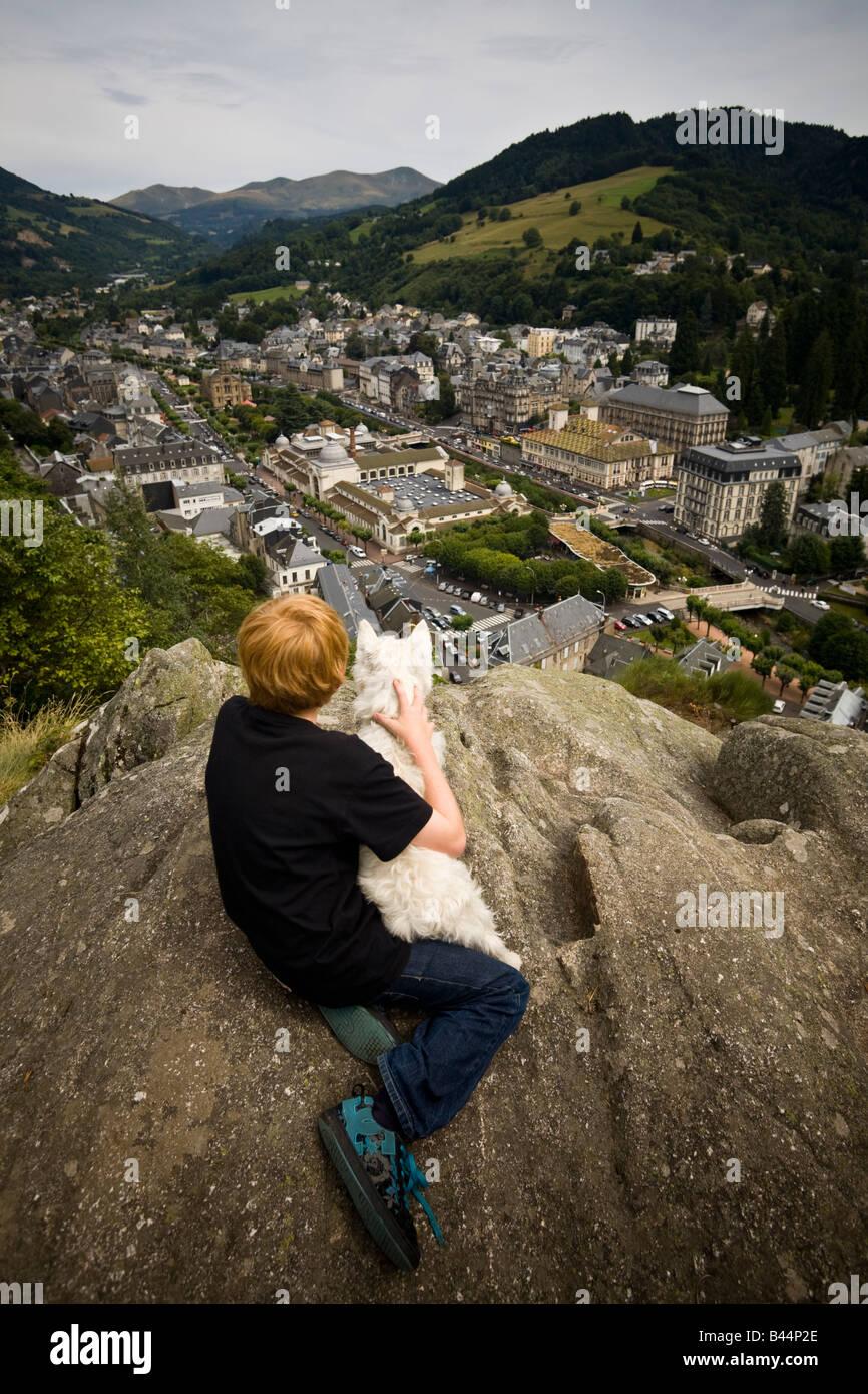 A young boy gazing at La Bourboule town with his dog. Jeune garçon contemplant avec son chien la ville de La Bourboule. Stock Photo