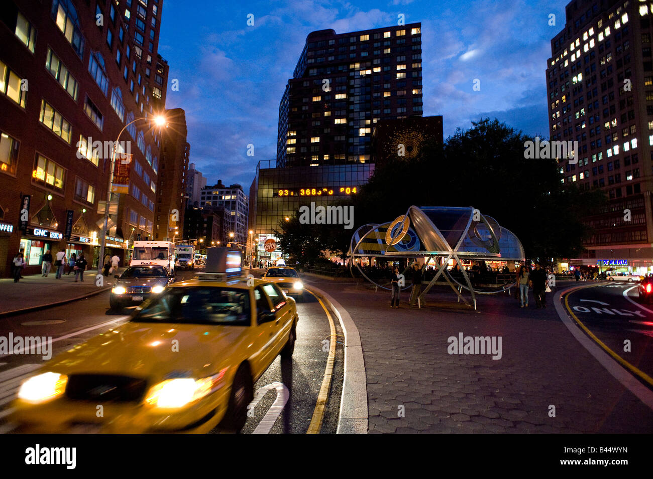 New York yellow cab at Union Square in the evening with clock of the Metronome in the background - Stock Image