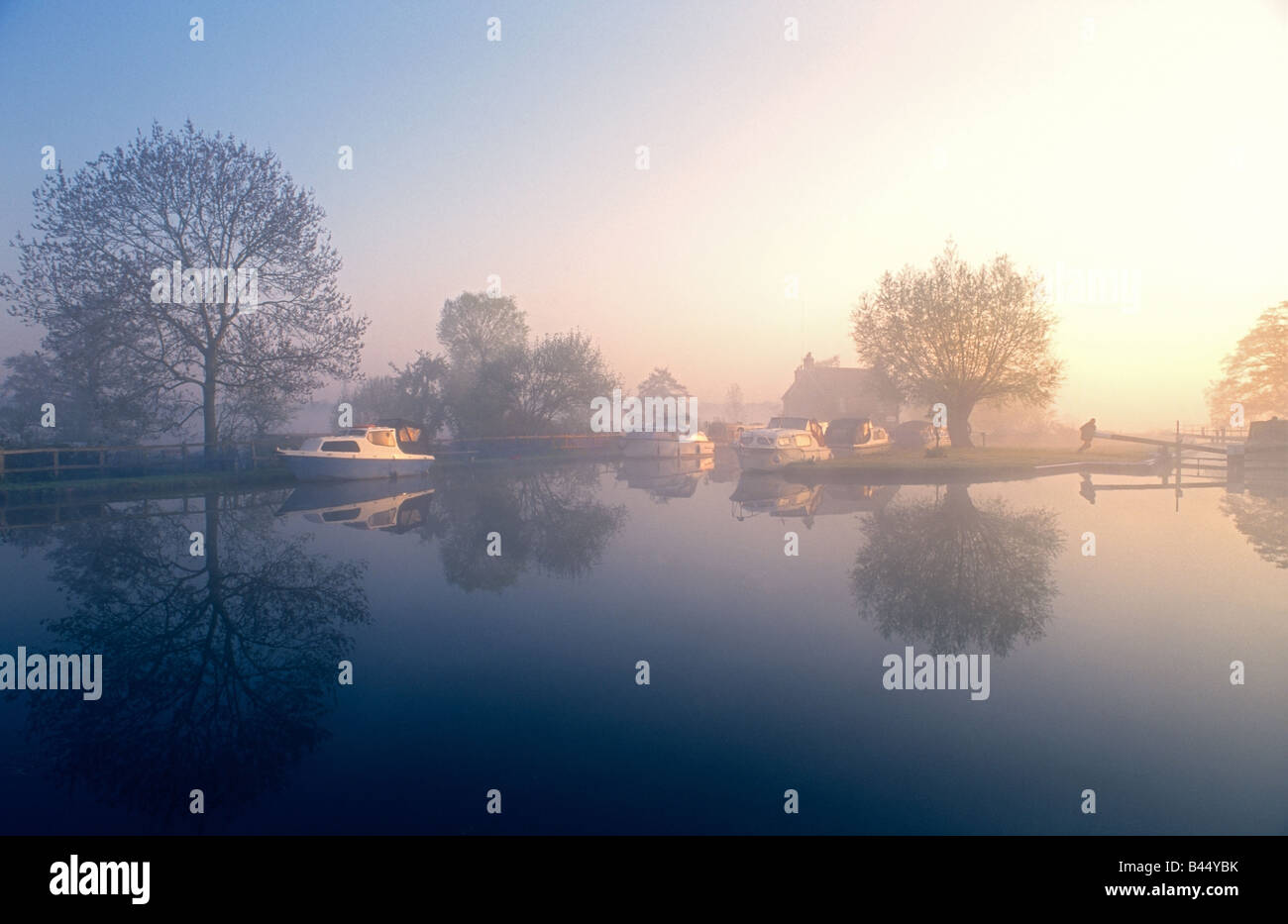 Papercourt Lock on a still misty sunrise with boat crew member operating the lock gates River Wey Surrey UK Stock Photo