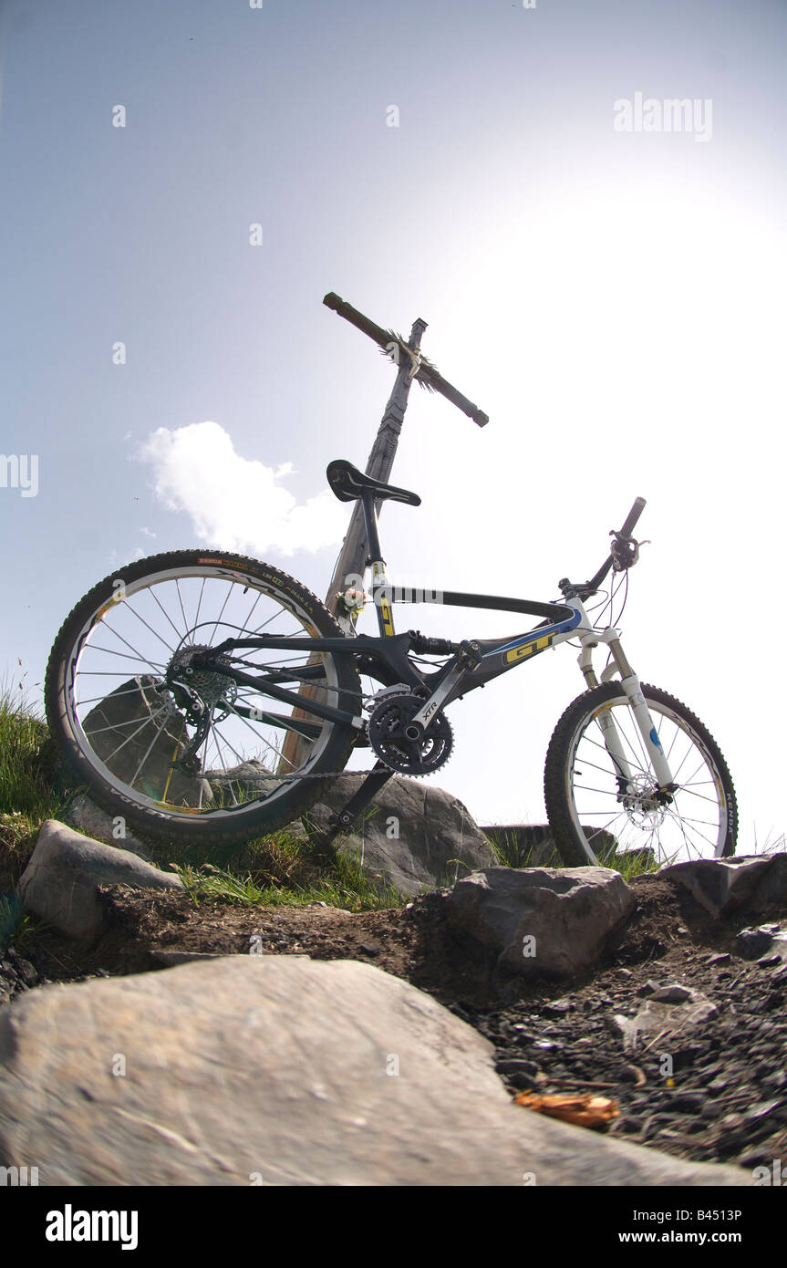 Mountain bike leant against a cross above Livigno, italy. - Stock Image