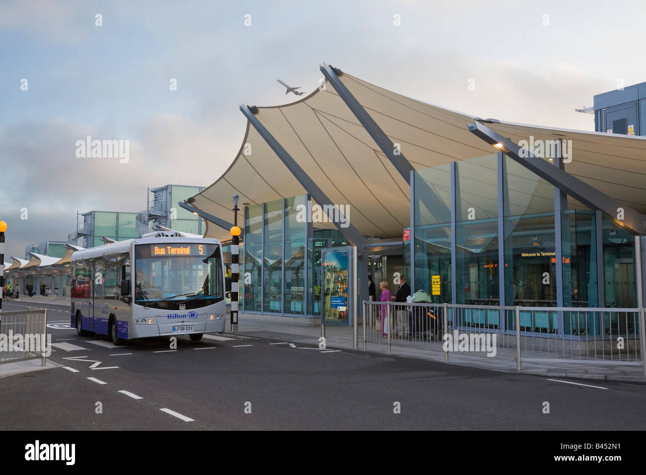 London Heathrow Airport British Airways Terminal 5 building international departures entrance and Hotel Hopper bus - Stock Image