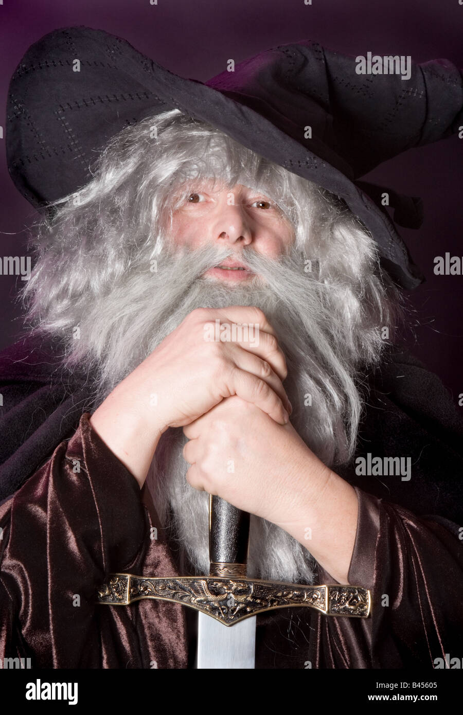 Halloween wizard leaning on a magical sword - Stock Image