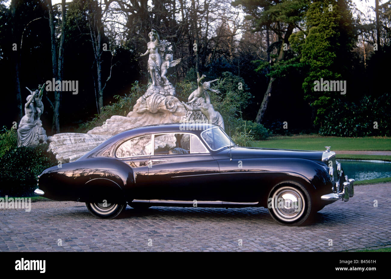 Classic 1955 Bentley R-Type Continental Fastback at sunset with ornate fountain at Cliveden Hotel Taplow Berkshire - Stock Image