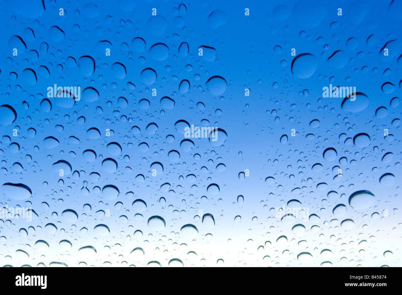 Rain droplets on blue tinted automobile windshield. - Stock Image