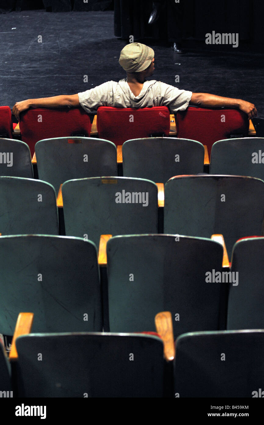 A spectator in a theatre sits in the front row in front of the stage. - Stock Image
