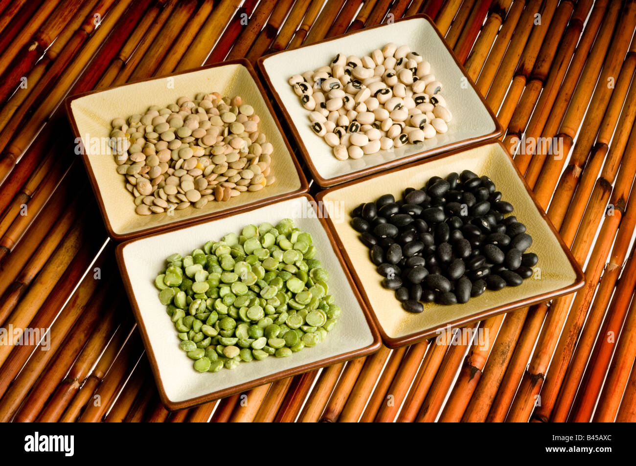 four dishes of lentils, peas, beans, black eyed peas on bamboo Stock Photo