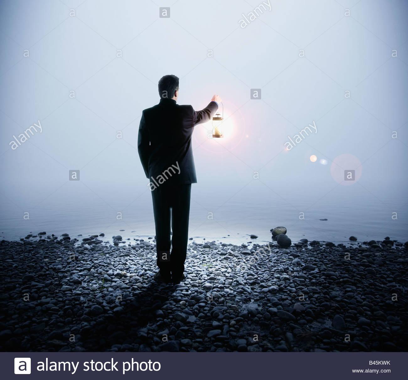 Portuguese businessman holding lantern next to water Stock Photo
