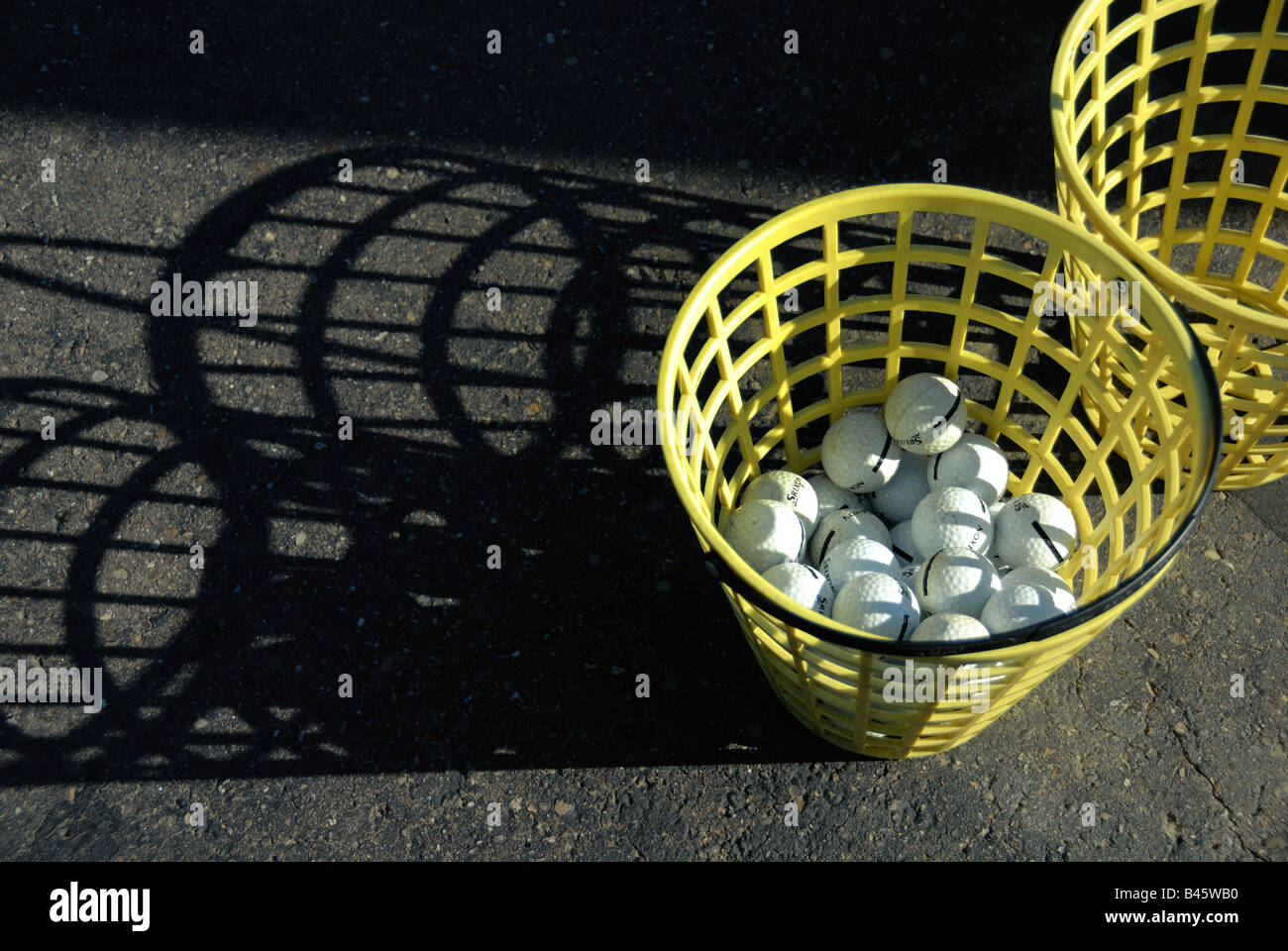 A bucket of golf balls at a golf driving range casts interesting shadows in the midday sun.Stock Photo
