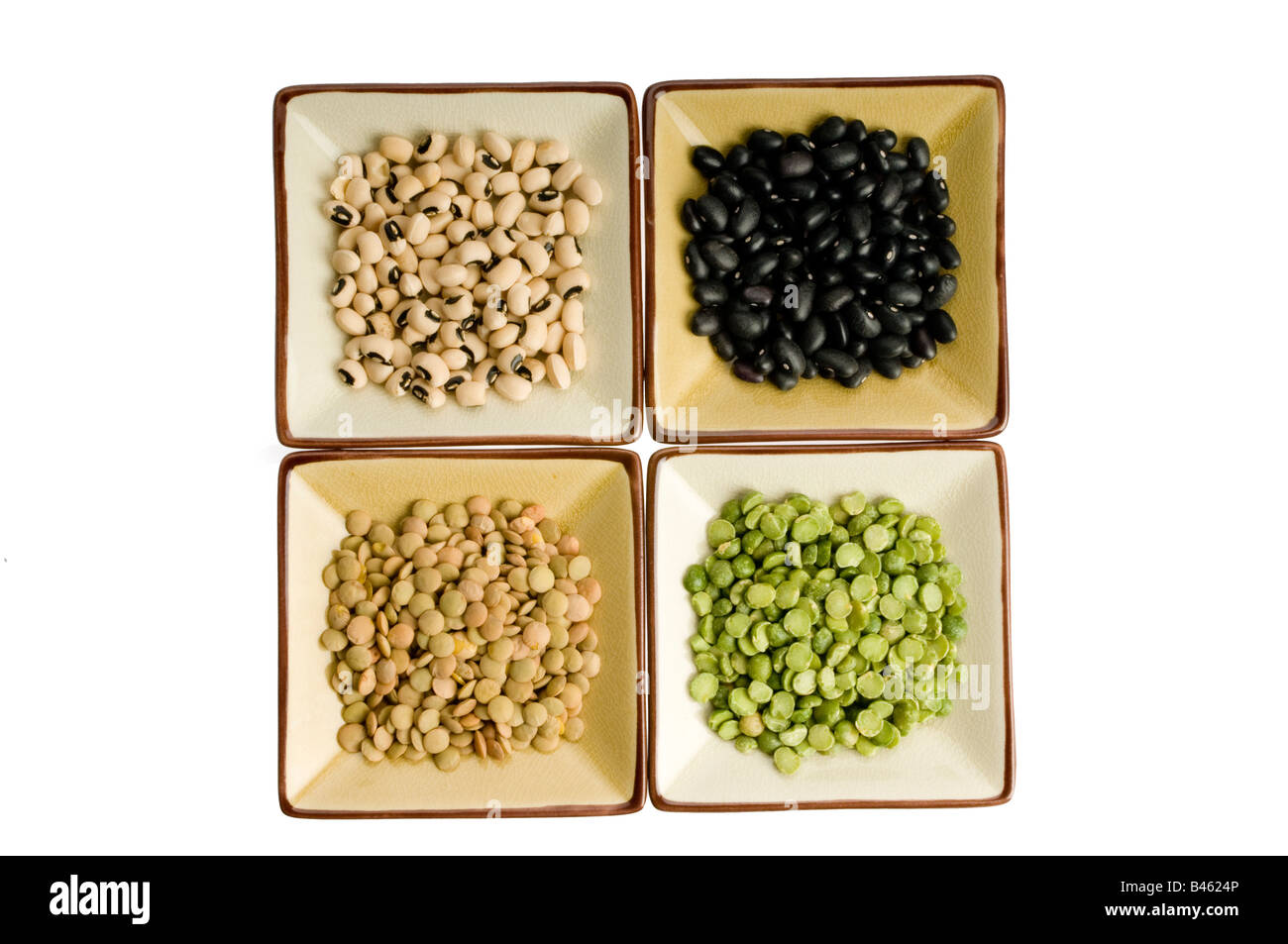 Four plates with lentils, black beans, black eyed peas, split peas - Stock Image