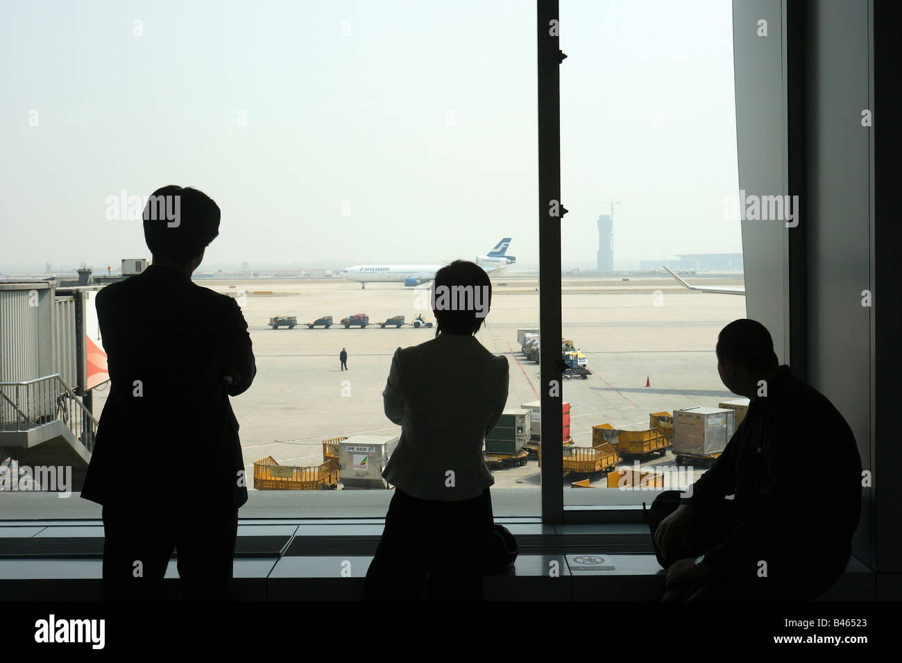 Three people looking at the airside of the airport in Beijing, China - Stock Image