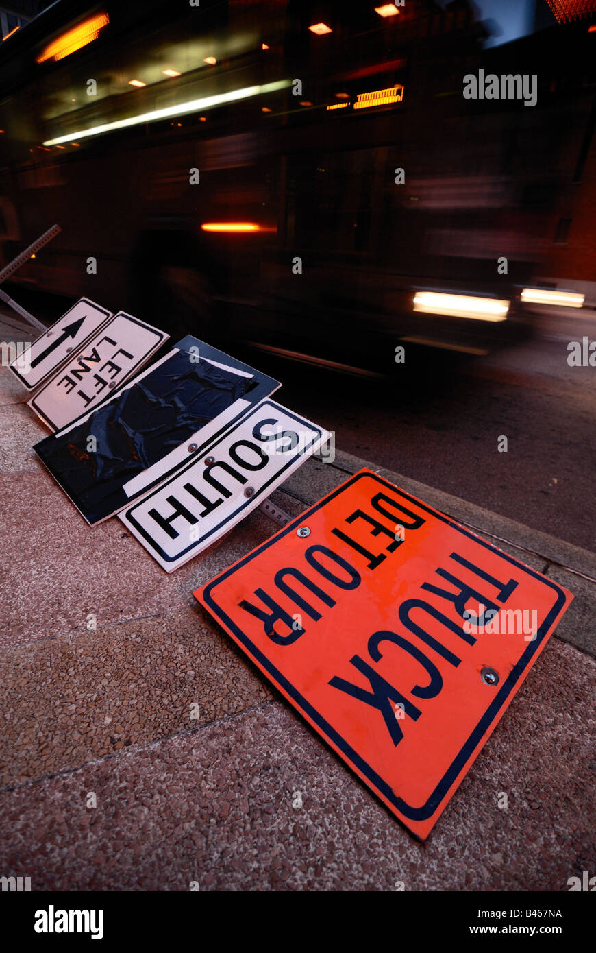 A detour sign that has been knocked over is lying on the sidewalk as a fast moving bus passes by. - Stock Image