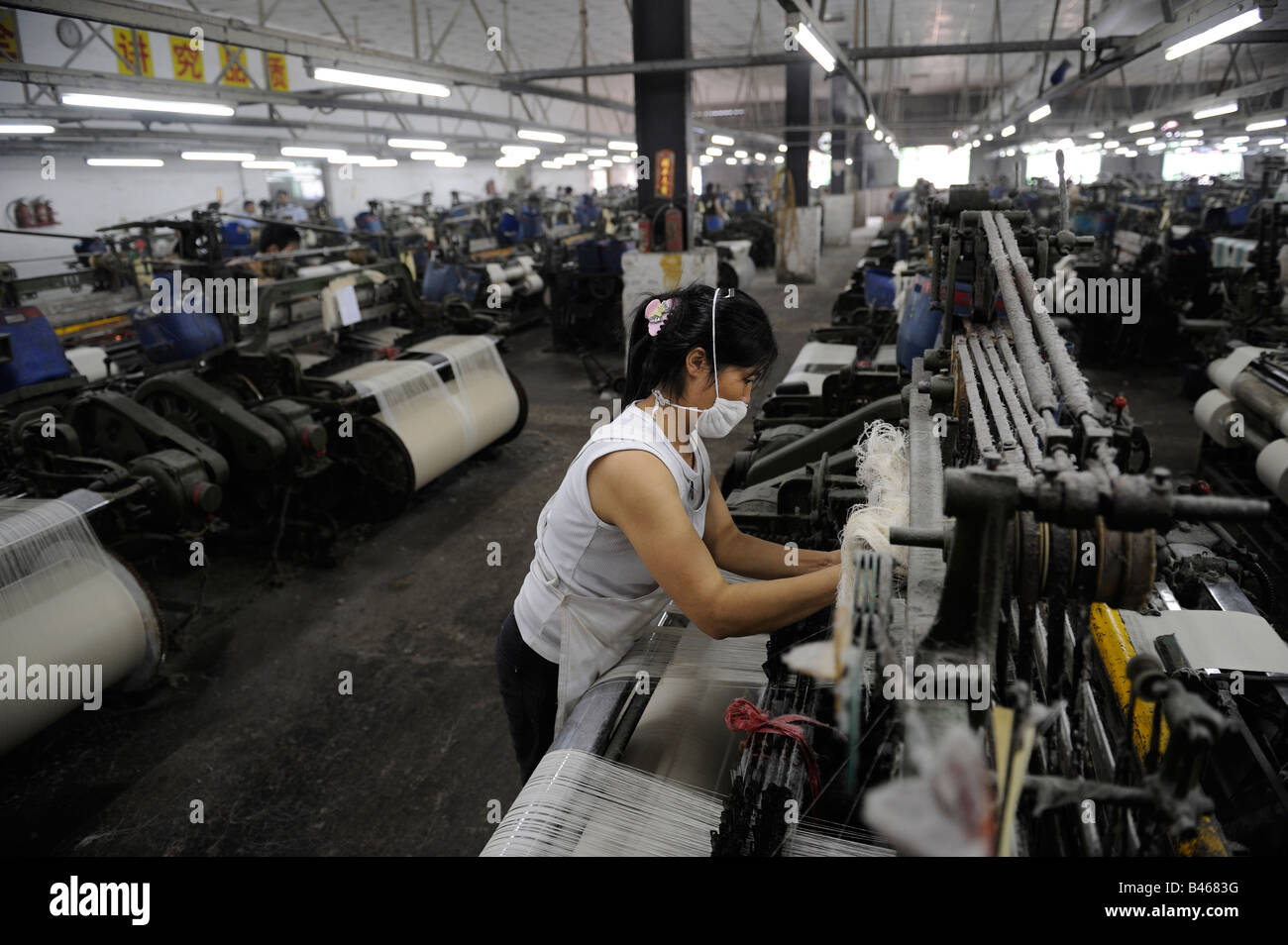 Female worker operating machine at a textile factory in Dongguan, Guangdong, China. 19-Sep-2008 - Stock Image