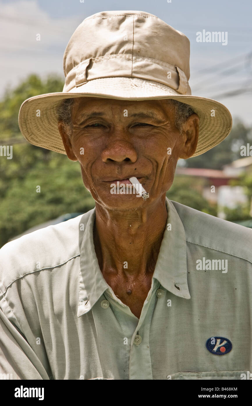 Cambodian man wearing a hat and smoking a cigarette Stock Photo