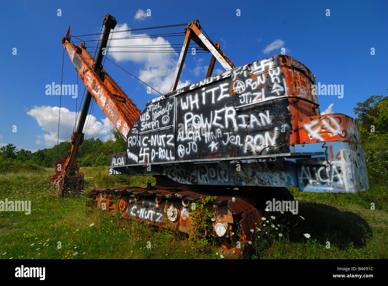 An abandoned steam shovel outside of Uniontown, Pennsylvania is covered in racist graffiti and slurs. - Stock Image