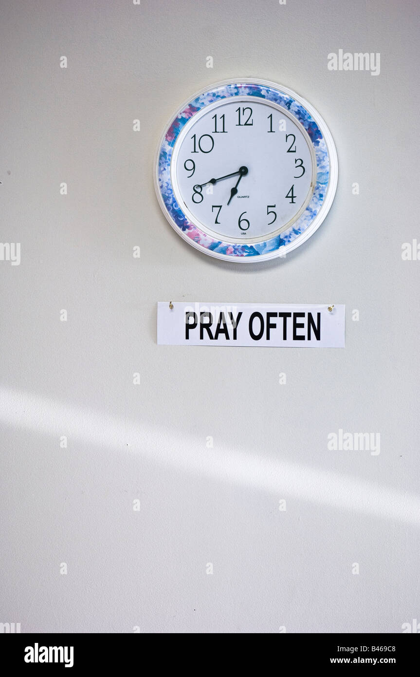 Pray often reminder sign under clock - Stock Image