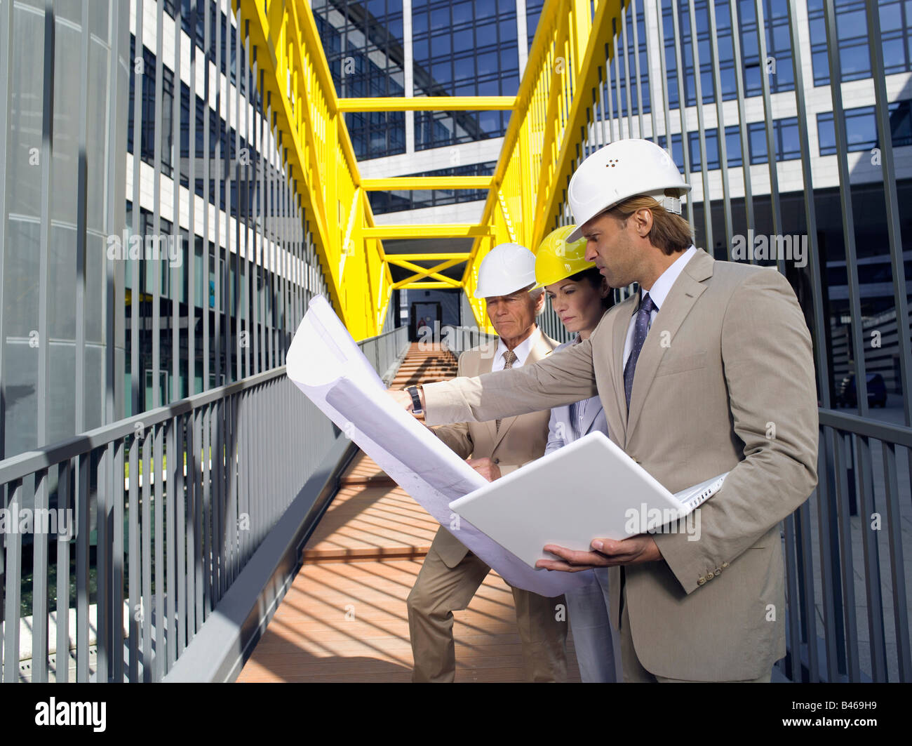 Germany, Baden Württemberg, Stuttgart, Men and woman in hard hats looking at blueprints - Stock Image
