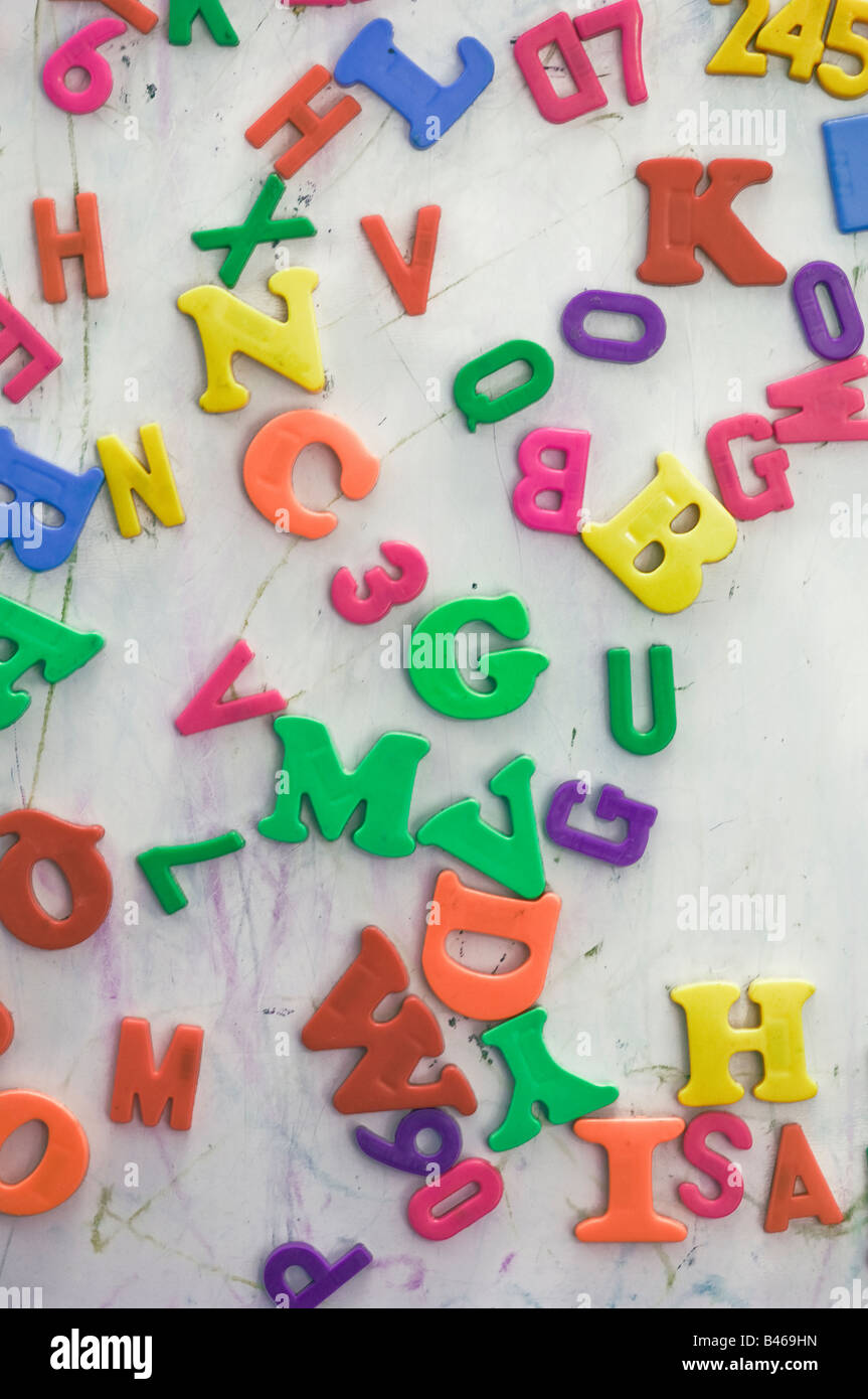 mixed up magnetic numbers and letters on a magnetic board - Stock Image