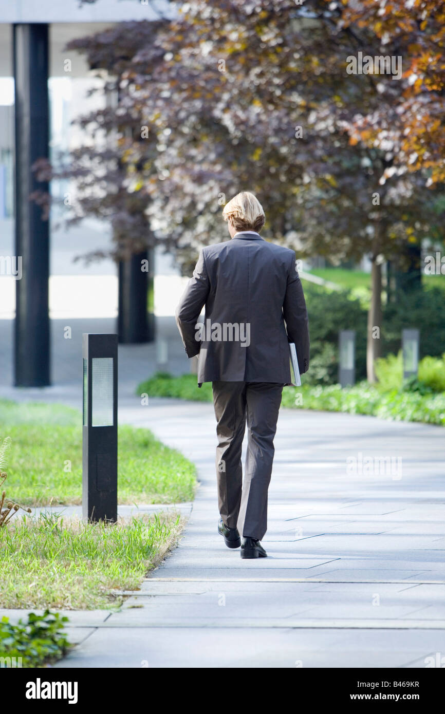 Germany, Baden Württemberg, Stuttgart, Business man walking along street, rear view - Stock Image