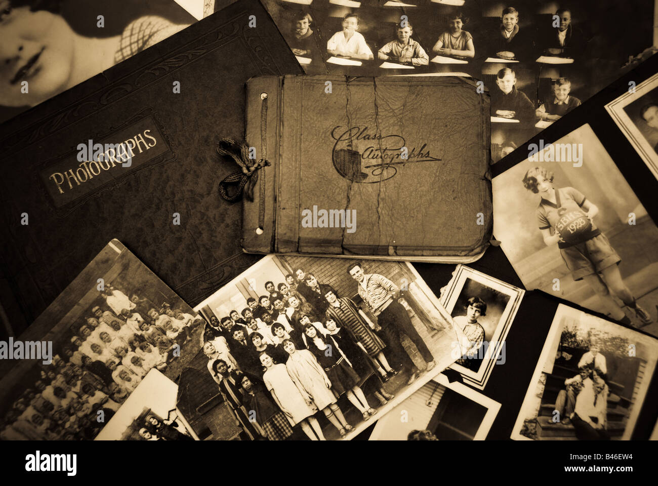 A collection of vintage class photos with an antique photo album and class autograph book - Stock Image