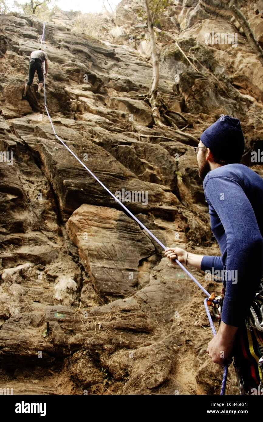 Two climbers on belay rope one holding and one climbing Nepal - Stock Image