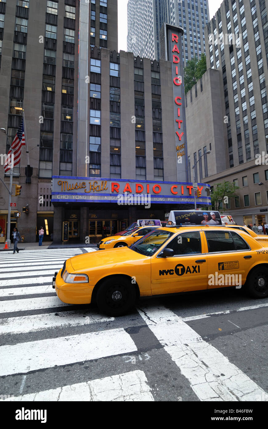 Yellow cabs pass over a crosswalk in front of Radio City Music Hall in New York City. - Stock Image