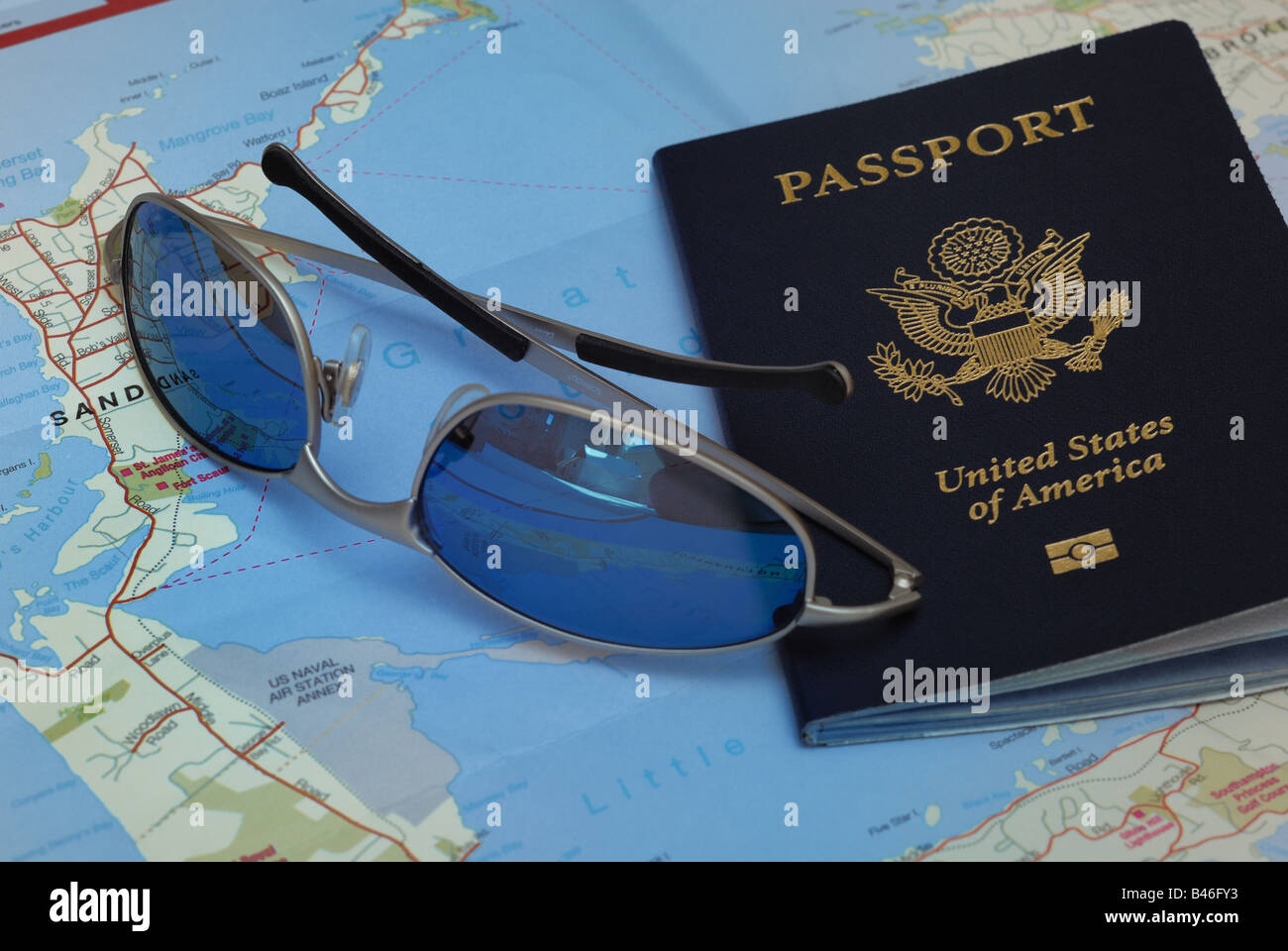 A United States Passport, sunglasses, and a folded map of Bermuda ...