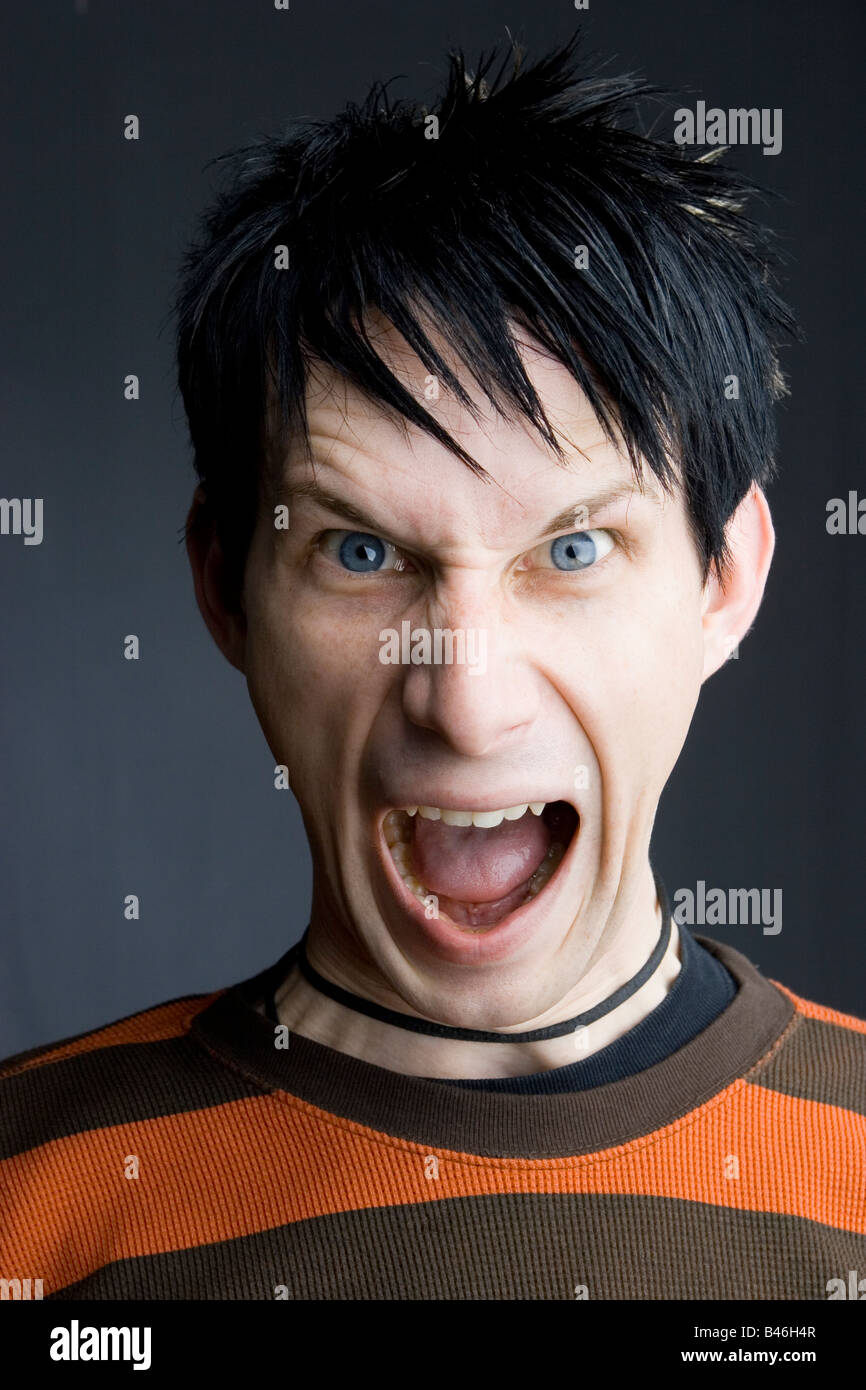 Young man with angry face, possibly shouting. - Stock Image