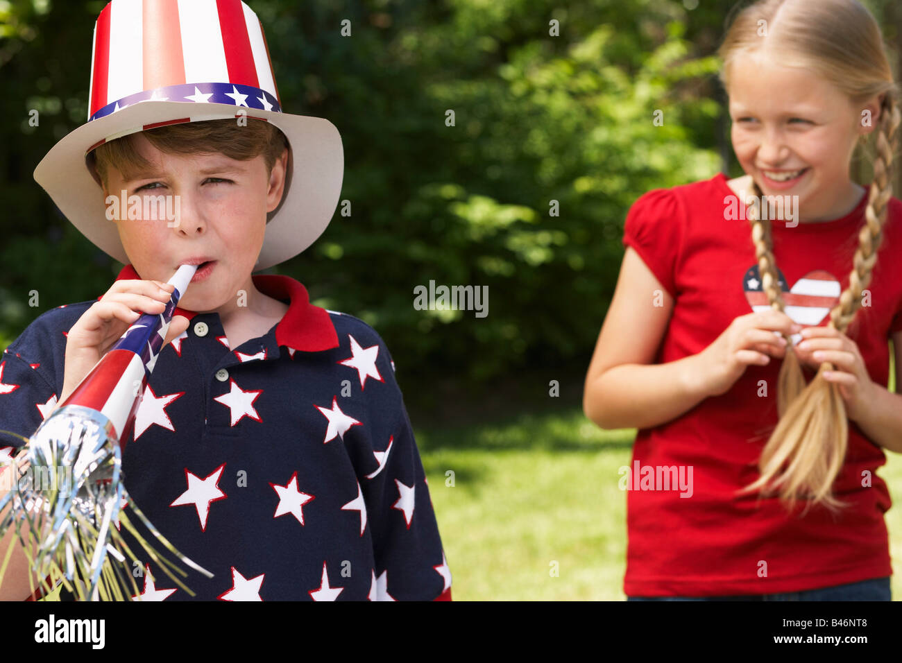 Portrait of Boy Wearing Stars and Stripes Top and Hat, Blowing Noisemaker Horn, Girl Watching Stock Photo