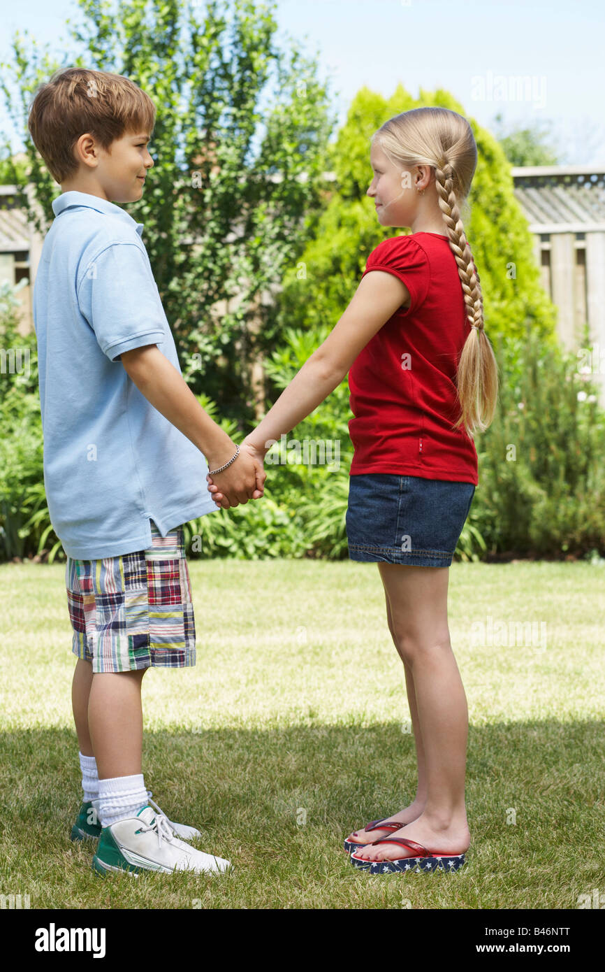 Sideview of Boy and Girl Standing in Backyard Holding Hands Stock Photo