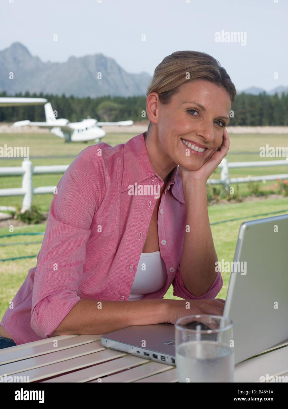 Woman on airfield with laptop - Stock Image
