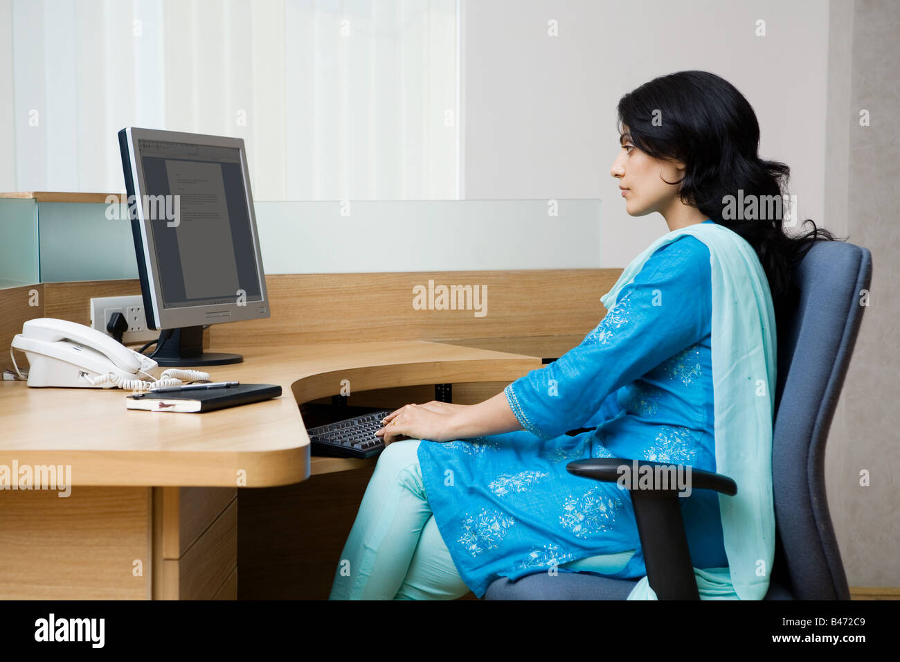 Indian woman working at her desk - Stock Image