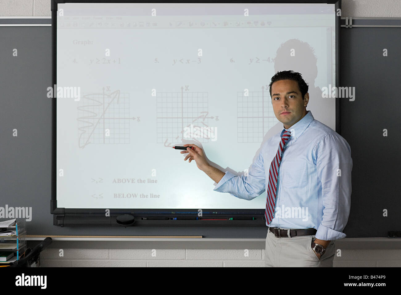 A teacher pointing at a projector screen - Stock Image