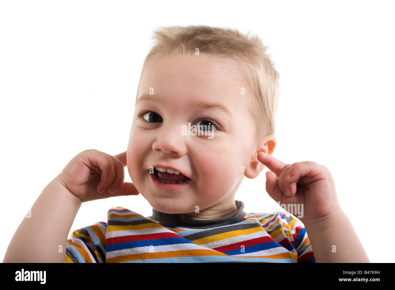 A toddler with his fingers in his ears - Stock Image