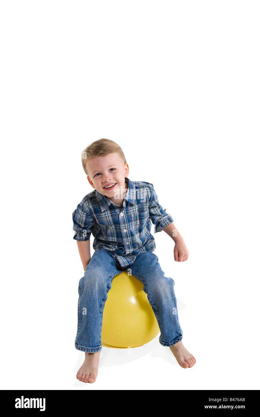 A boy sitting on a ball - Stock Image
