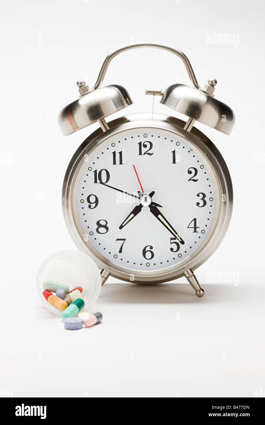 Alarm clock and a container of tablets - Stock Image